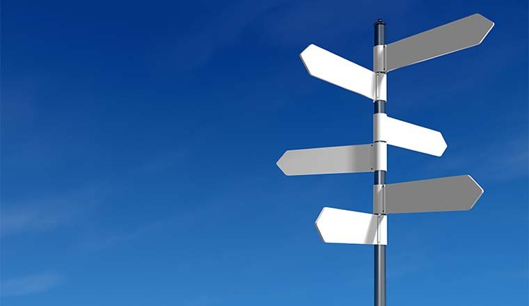 Blue sky background with a white signpost with arrows pointing in various directions